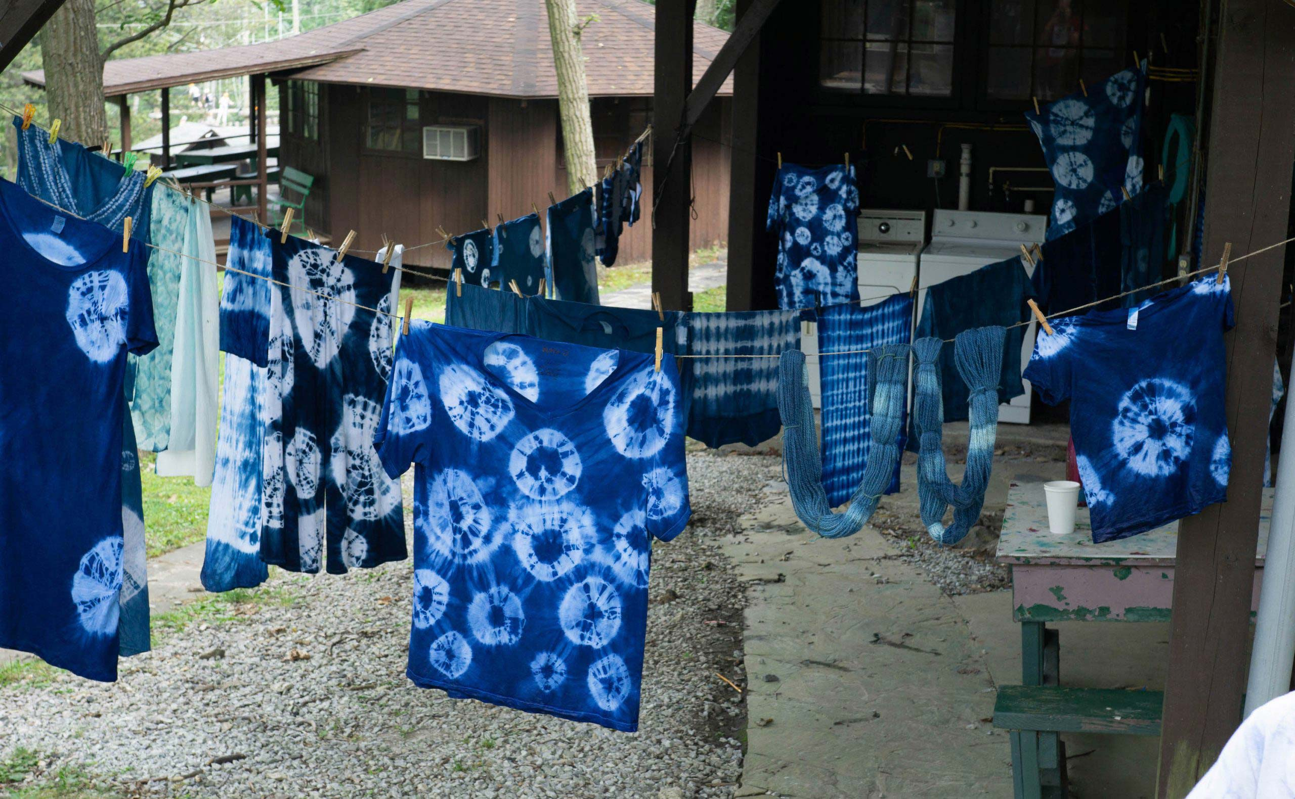 A clothesline of drying shirts dyed with indigo