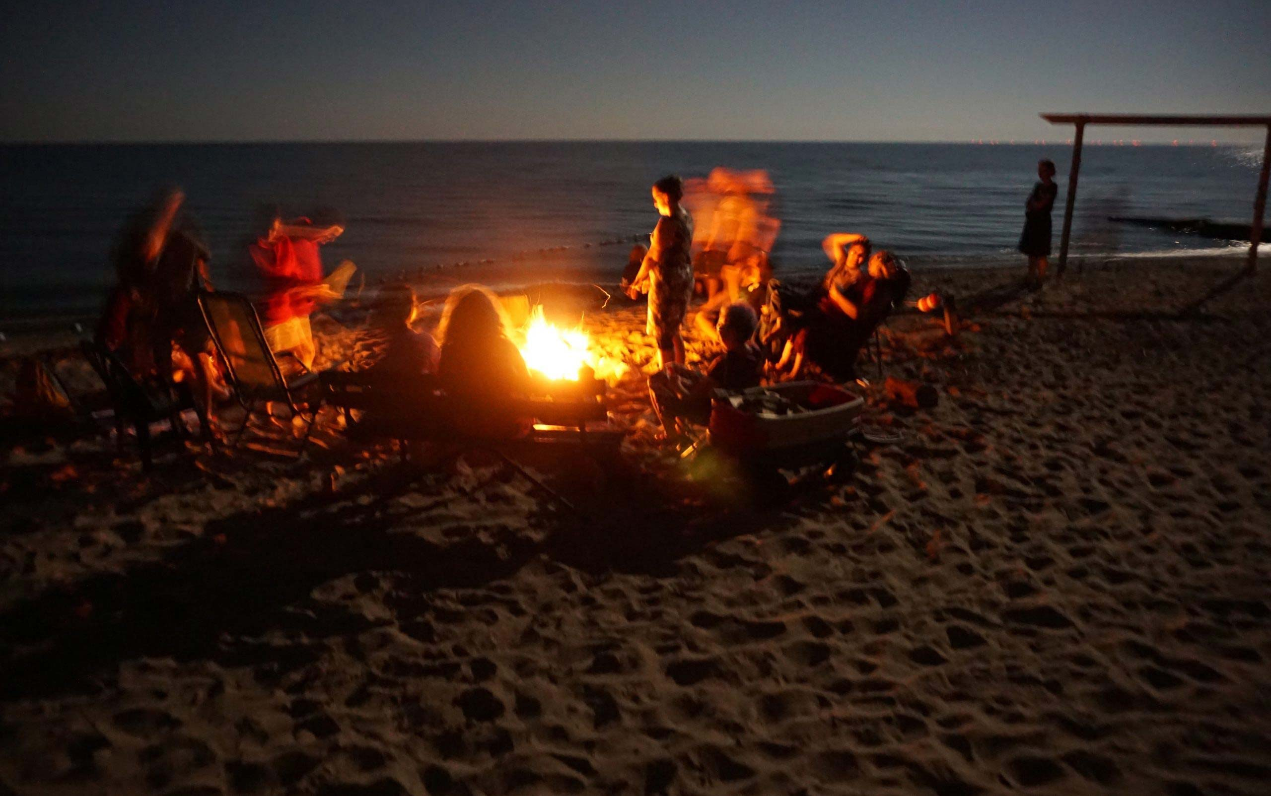 Campers gathered around a bonfire on the beach